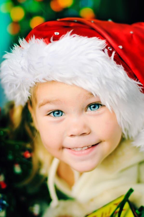 Portret van het gelukkige meisje van Kerstmis in de hoed van de Kerstman stock foto's