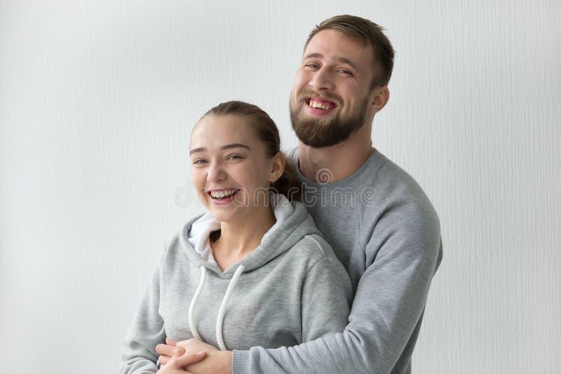 Portret van het gelukkige millennial paar stellen in eigen flat royalty-vrije stock afbeelding