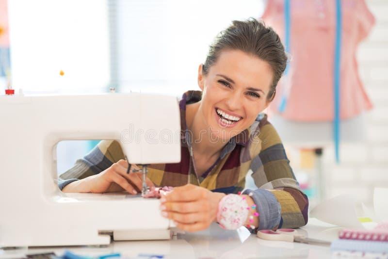 Portret van het gelukkige naaister naaien in studio stock afbeeldingen