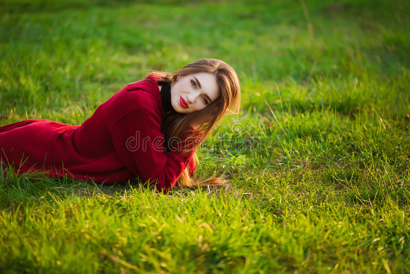 Portret van het gelukkige sportieve vrouw ontspannen in park op groene weide Blij vrouwelijk model die verse lucht in openlucht a royalty-vrije stock foto