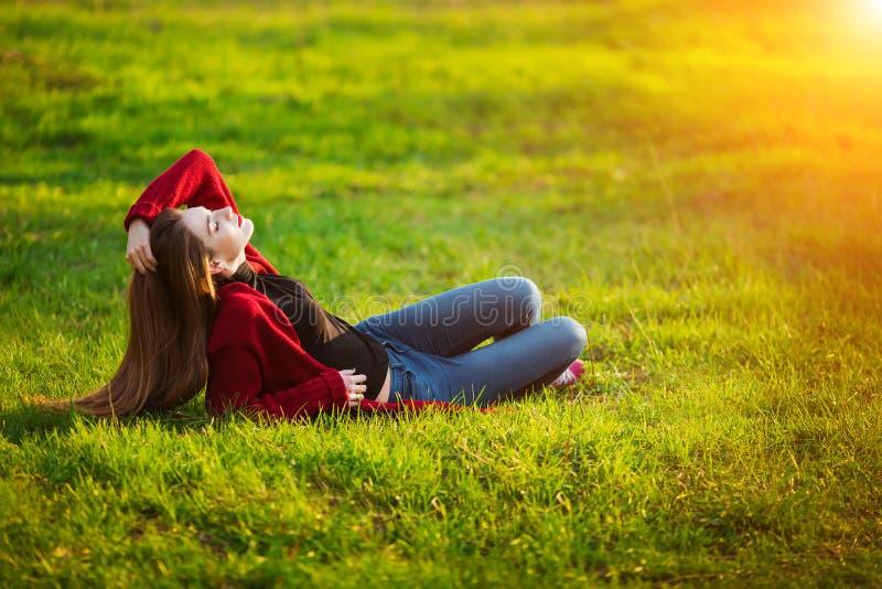 Portret van het gelukkige sportieve vrouw ontspannen in park op groene weide Blij vrouwelijk model die verse lucht in openlucht a stock afbeeldingen