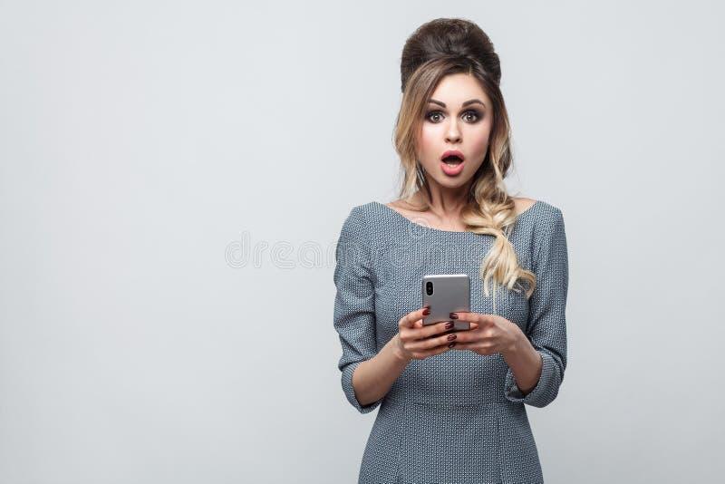 Portret van het geschokte mooie bloggertiener dragen in grijze kleding met vlecht bij hoofd status, het gebruiken van smartphone  royalty-vrije stock foto