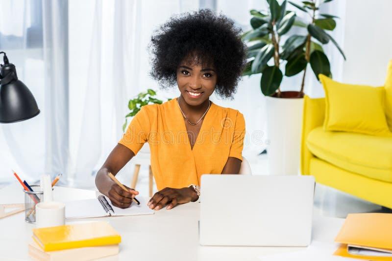 portret van het glimlachen Afrikaanse Amerikaanse freelancer bij werkplaats met laptop en notitieboekje royalty-vrije stock foto