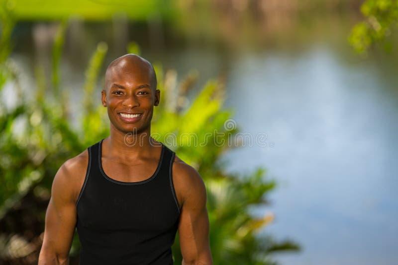 Portret van het glimlachen het Afrikaanse Amerikaanse geschiktheid model in openlucht stellen stock fotografie