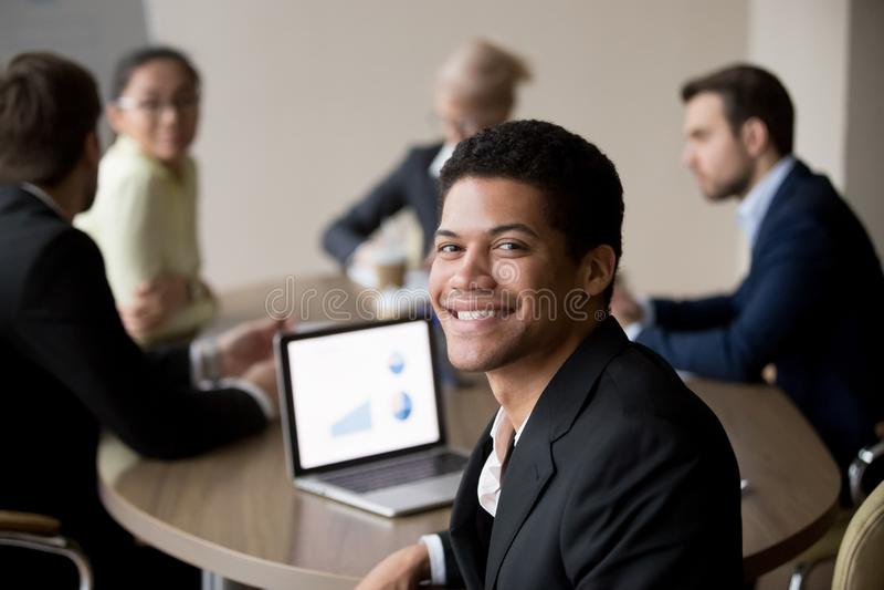 Portret van het glimlachen het Afrikaanse Amerikaanse werknemer stellen op vergadering stock foto