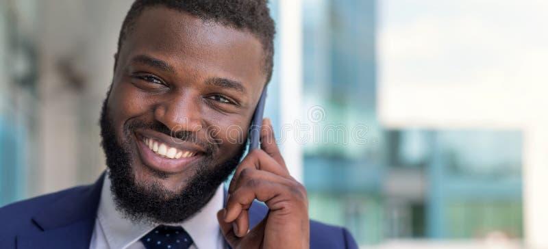 Portret van het glimlachen het Afrikaanse Amerikaanse zakenman spreken telefonisch in openlucht De ruimte van het exemplaar stock afbeelding