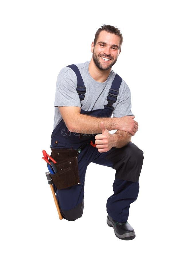 Portret van het glimlachen arbeider het knielen met hand die o.k. gebaar doen royalty-vrije stock afbeelding