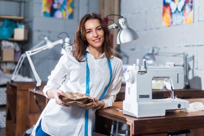Portret van het glimlachen Europese manierontwerper status naast naaimachine die een gift houden die in ambachtdocument binnen wo royalty-vrije stock fotografie