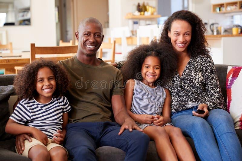 Portret van het Glimlachen Familiezitting op Sofa At Home Relaxing Together stock afbeelding