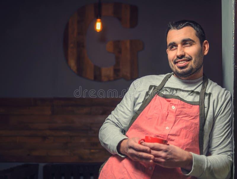 Portret van het glimlachen gebaarde baristas in een rode schort royalty-vrije stock afbeelding