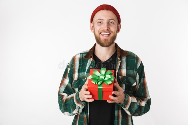 Portret van het glimlachen van gebaarde kerel die hoed en plaidoverhemd dragen die huidige doos houden, terwijl status geïsoleerd royalty-vrije stock afbeeldingen