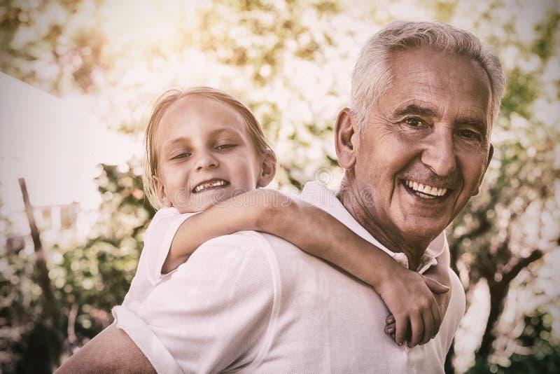 Portret van het glimlachen grootvader het dragen kleindochtervervoer per kangoeroewagen royalty-vrije stock foto's