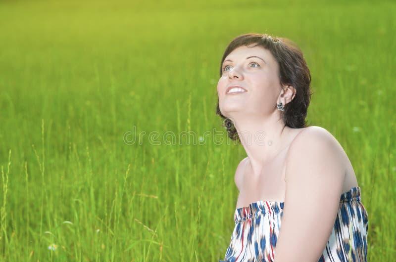 Portret van het Glimlachen het Kaukasische Donkerbruine Vrouw Stellen in openlucht op Aardachtergrond stock afbeelding