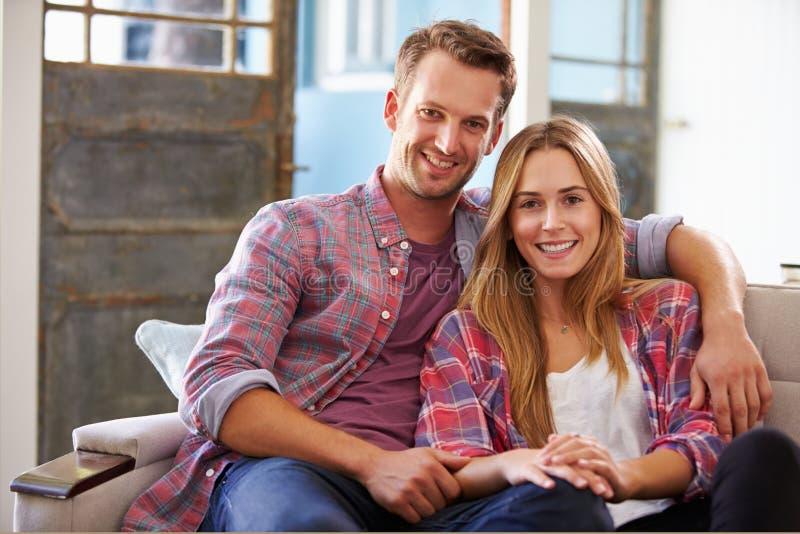 Portret van het Glimlachen Jonge Paarzitting op Sofa At Home stock afbeelding