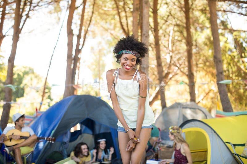 Portret van het glimlachen jonge vrouw status met vrienden die op achtergrond zitten stock afbeeldingen