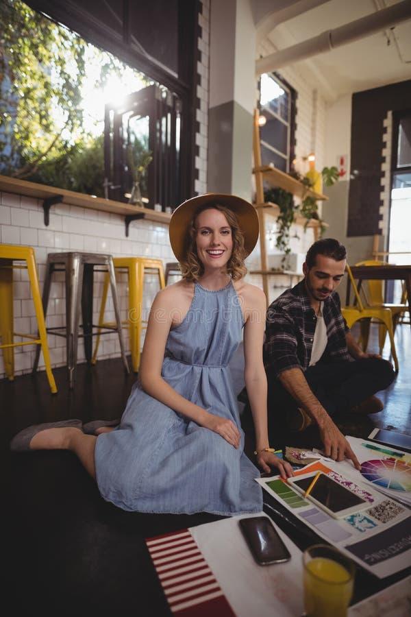 Portret van het glimlachen jonge vrouwelijke professionele zitting met mannelijke collega stock afbeelding