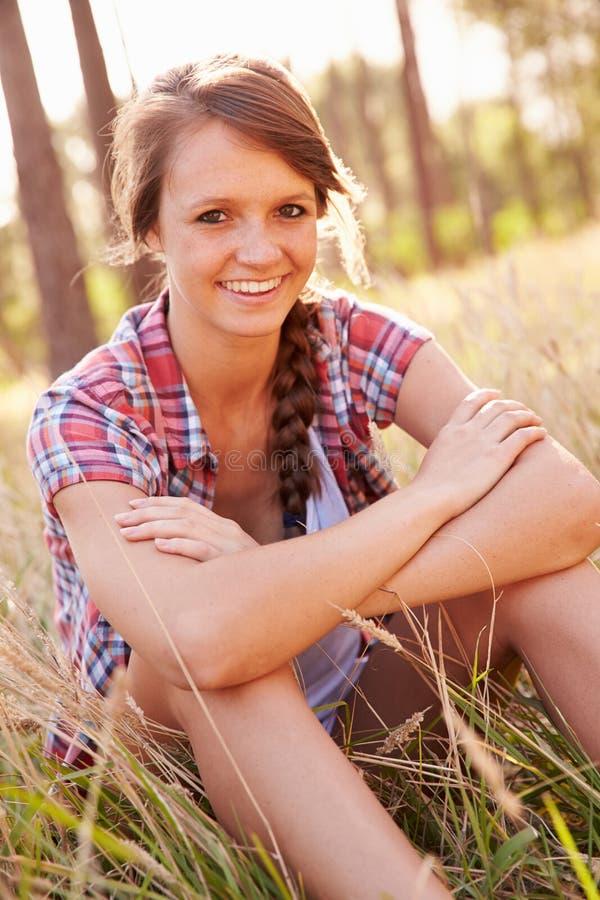 Portret van het Glimlachen Jonge Vrouwenzitting in Platteland royalty-vrije stock afbeeldingen