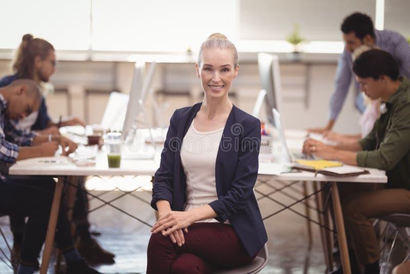 Portret van het glimlachen onderneemsterzitting op stoel met team die op achtergrond werken stock afbeelding