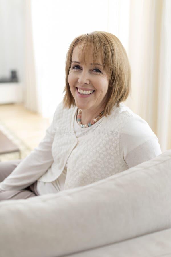Portret van het Glimlachen Rijpe Vrouwenzitting op Sofa At Home stock foto's