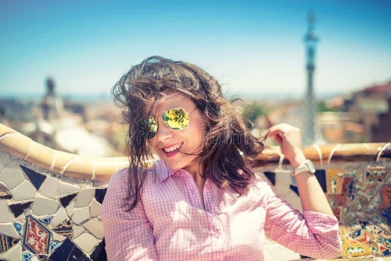 Portret van het glimlachen, schitterend donkerbruin meisje met zonnebril op een winderige dag stock foto