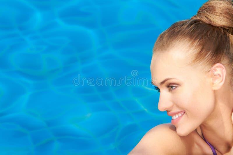 Portret van het glimlachen schoonheid op blauw water stock afbeelding