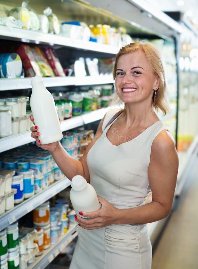 Portret van het glimlachen van de fles van de vrouwenholding met verse melk royalty-vrije stock fotografie