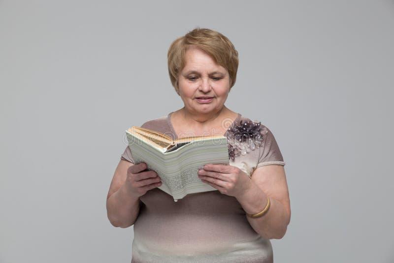 Portret van het glimlachen van het hogere boek van de vrouwenlezing stock afbeeldingen