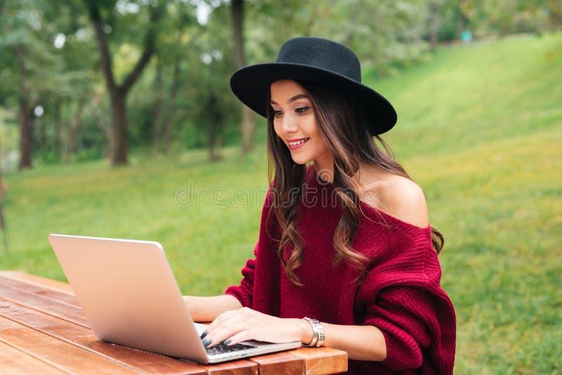 Portret van het glimlachen van vrij Aziatisch meisje die laptop computer met behulp van royalty-vrije stock afbeelding