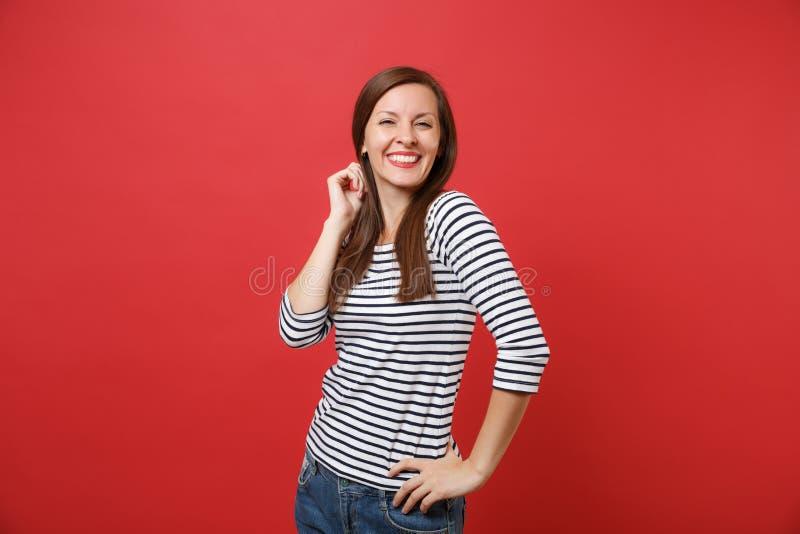 Portret van het glimlachen van vrij jonge vrouw in toevallige gestreepte kleren die houdend hand dichtbij hoofd bevinden die op h stock foto's