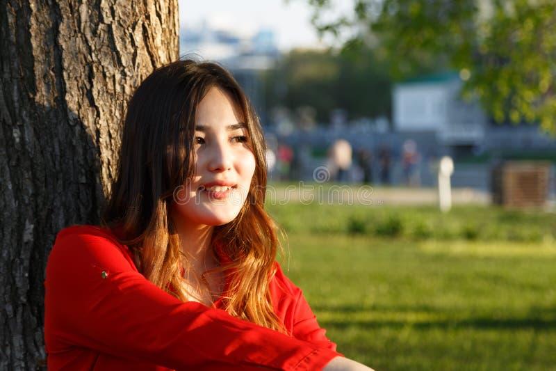 Portret van het glimlachen het vrolijke jonge Aziatische vrouw leunen tegen boom stock foto