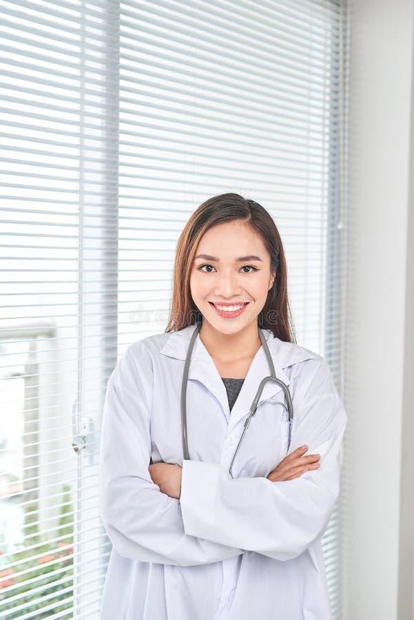 Portret van het glimlachen het vrouwelijke arts bevindende stellen in haar het ziekenhuisbureau , Gezondheidszorg en medisch bero royalty-vrije stock fotografie