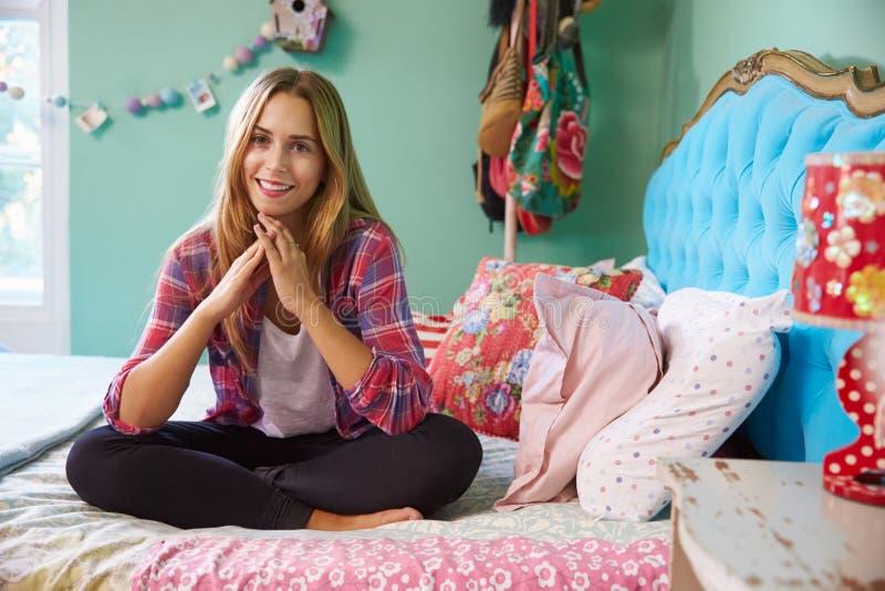 Portret van het Glimlachen Vrouwenzitting op Bed thuis stock fotografie