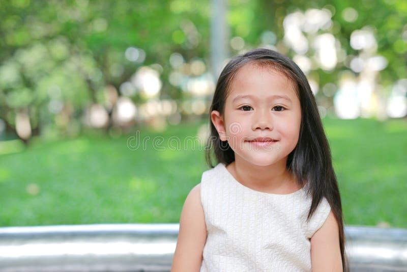 Portret van het glimlachen van weinig Aziatisch jong geitjemeisje in aardpark met het kijken camera royalty-vrije stock afbeelding