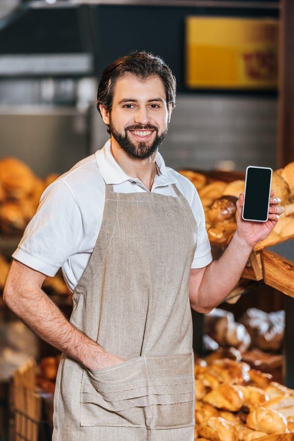 portret van het glimlachen winkel hulp het tonen smartphone met het lege scherm stock foto's