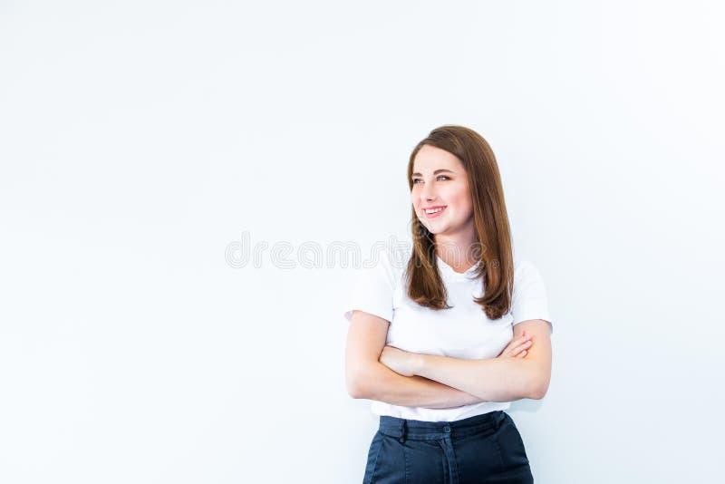 Portret van het glimlachen zekere jonge Kaukasische vrouw status met gekruiste of gevouwen wapens en het bekijken weg exemplaar r stock fotografie