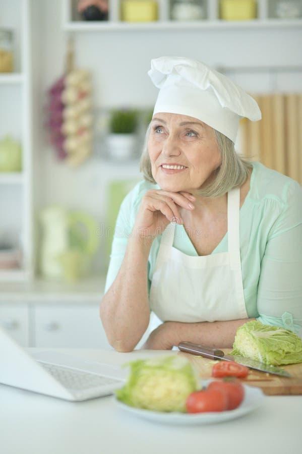 Portret van het hogere portret van de vrouwenchef-kok bij keuken stock foto's