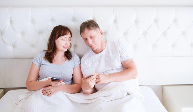 Portret van het houden van van midden oud paar die en op iets op een mobiele telefoon in slaapkamer glimlachen letten stock foto