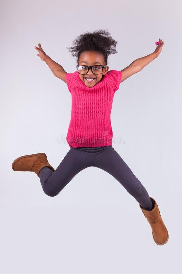Portret van het Jonge Afrikaanse Amerikaanse meisje springen stock afbeeldingen