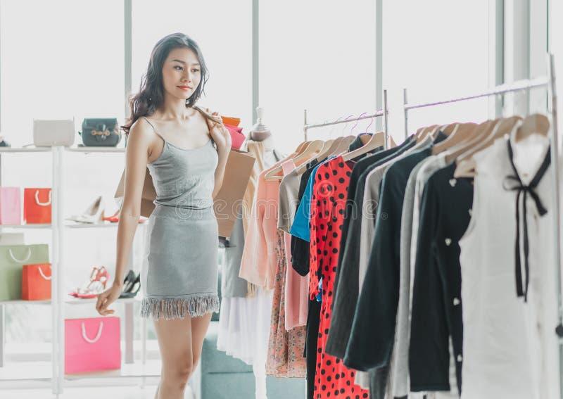 Portret van het jonge Aziatische vrouw winkelen voor sommige kleren bij een opslag het winkelen, manier, stijl en mensenconcept stock foto's