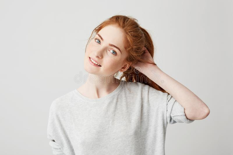 Portret van het jonge leuke roodharigemeisje glimlachen die camera wat betreft haar over witte achtergrond bekijken stock foto