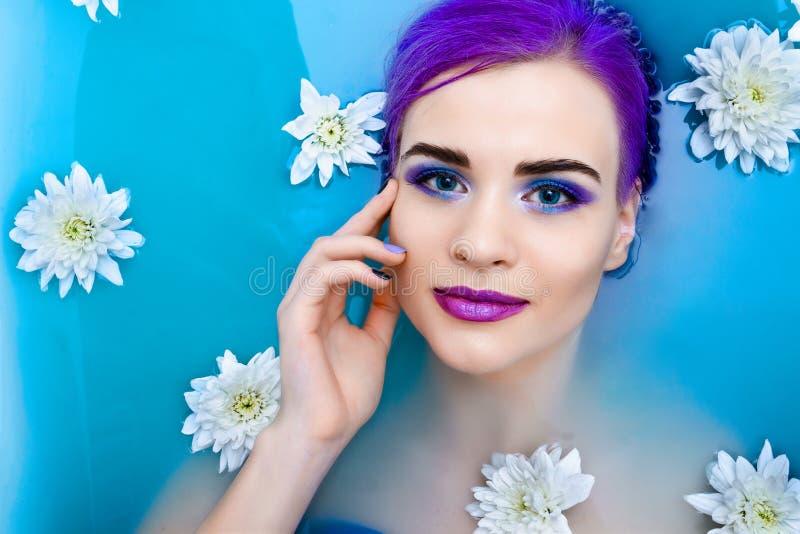 Portret van het jonge leuke vrouwelijke model van de manierluxe in badkuip met bloemen stock fotografie