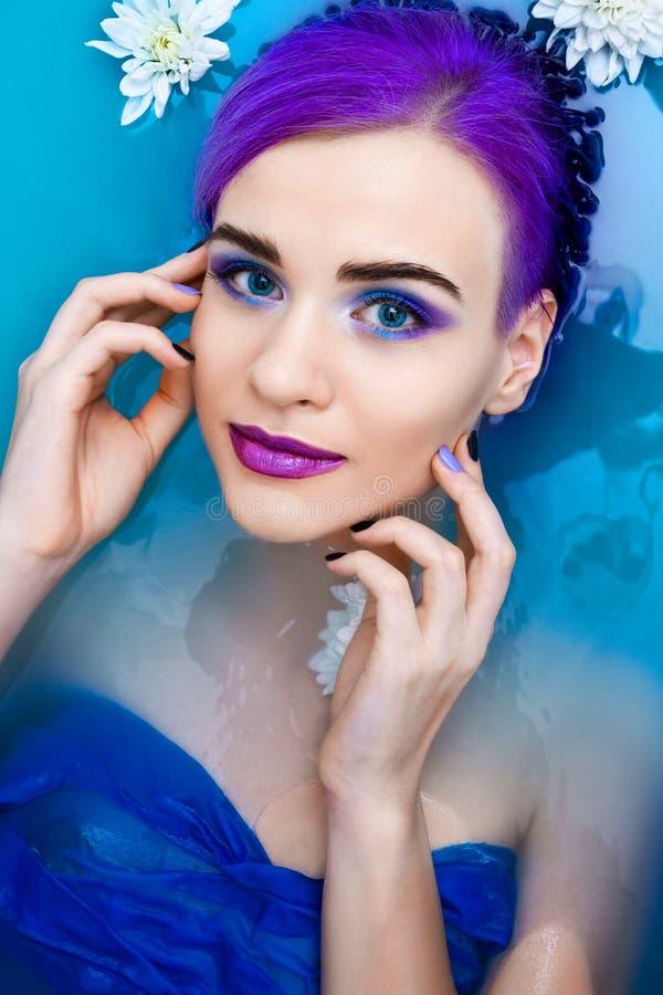 Portret van het jonge leuke vrouwelijke model van de manierluxe in badkuip met bloemen stock afbeeldingen