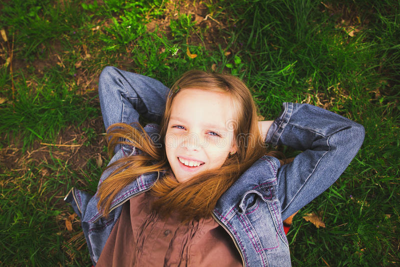 Portret van het jonge meisje leggen op gras in openlucht royalty-vrije stock afbeeldingen