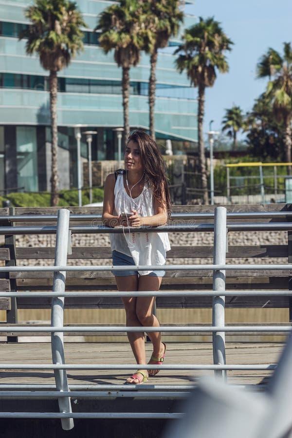 Portret van het jonge mooie donkerbruine meisje luisteren aan de muziek op de telefoon stock afbeeldingen