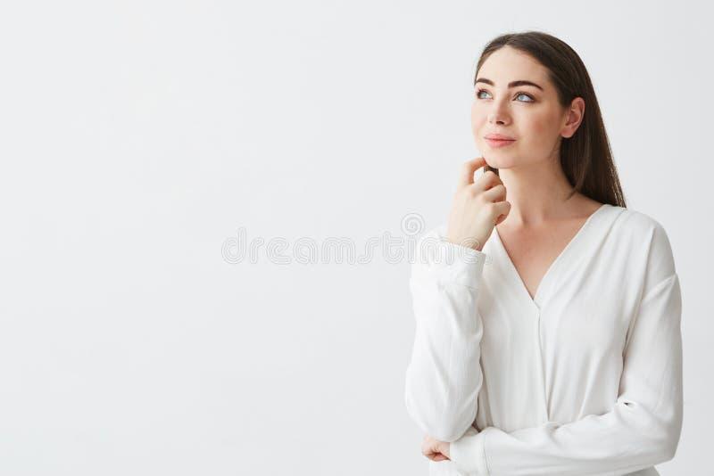 Portret van het jonge mooie donkerbruine onderneemster dromen die het fronsen over witte achtergrond denken Hand op kin royalty-vrije stock afbeelding