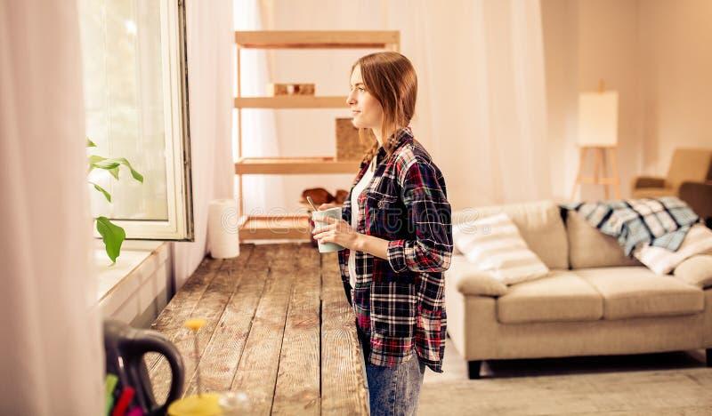 Portret van het jonge mooie meisje kijken door de kop thee of de koffie van de vensterholding royalty-vrije stock afbeelding