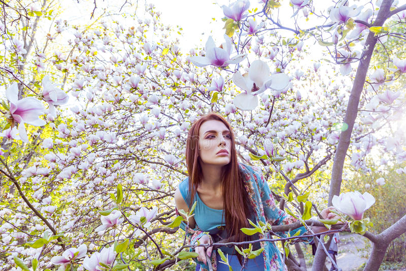 Portret van het jonge mooie vrouw stellen onder bloeiende bomen met roze oogschaduw royalty-vrije stock fotografie