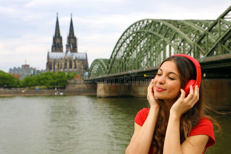 Portret van het jonge ontspannen vrouw luisteren aan muziek met stedelijke achtergrond Stadsmeisje die met rode hoofdtelefoon van royalty-vrije stock foto