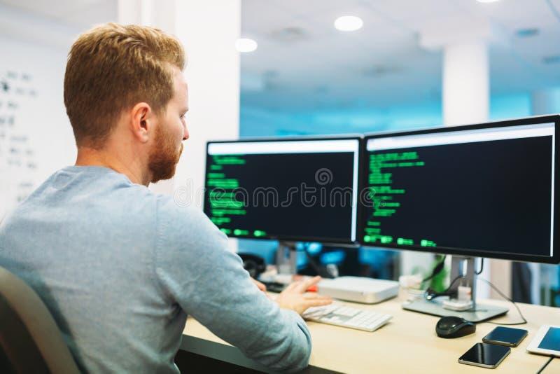 Portret van het jonge programmeur werken in bureau stock afbeeldingen