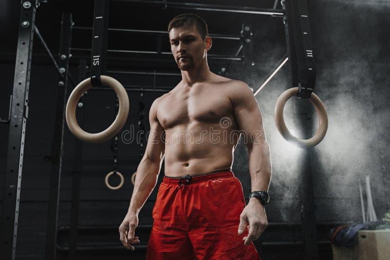 Portret van het jonge spiercrossfitatleet voorbereidingen treffen voor training bij de gymnastiek stock foto's